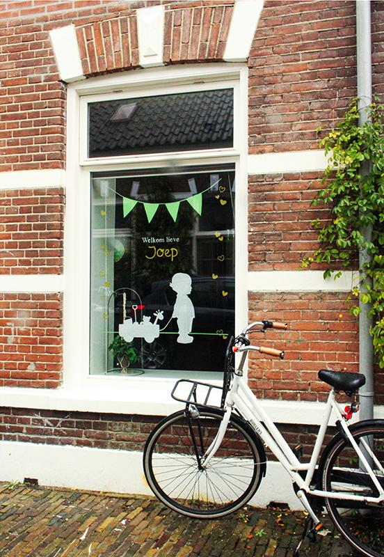 Huis met geparkeerde witte fiets voor. Raamtekening van vlaggetjes boven een jongen met knuffels in een kar.