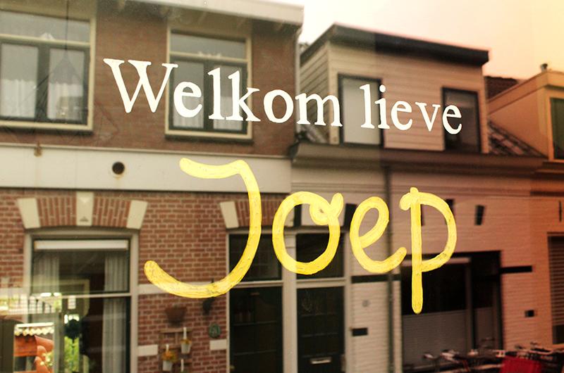 """Huizen weerspiegeld in raam. Raamtekening met tekst """"Welkom lieve Joep"""""""